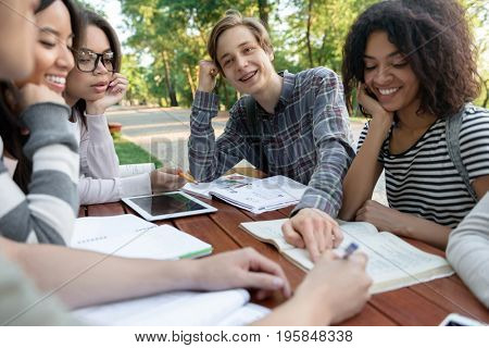 Photo of multiethnic group of cheerful young students sitting and studying outdoors while talking. Looking aside.