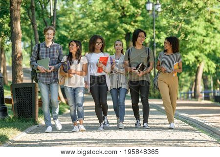 Multiethnic group of happy young people walking outdoors. Looking aside.