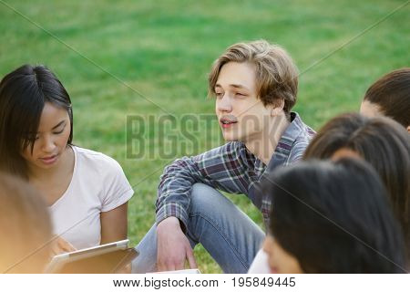Photo of multiethnic group of concentrated young students sitting studying outdoors. Looking aside.