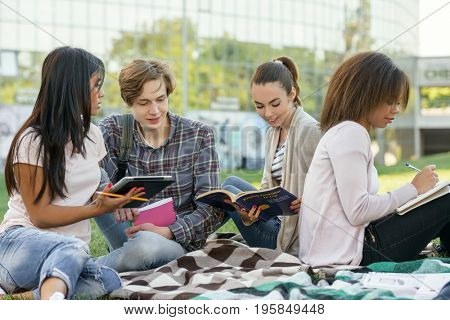 Image of multiethnic group of concentrated young students sitting studying outdoors. Looking aside.