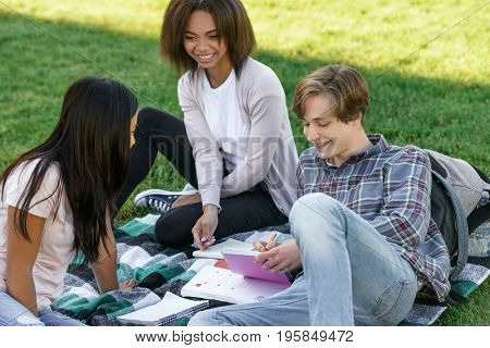 Picture of multiethnic group of happy young students sitting studying outdoors. Looking aside.