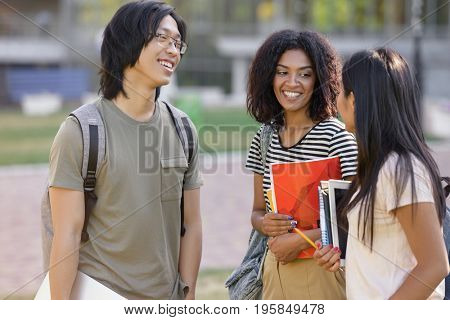 Picture of multiethnic group of young students standing outdoors talking. Looking aside.