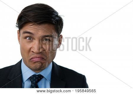 Portrait of businessman making a face against white background