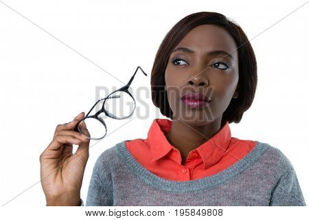 Woman looking away while holding eyeglasses against white background