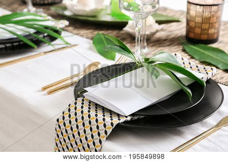 Beautiful table setting with green tropical leaves