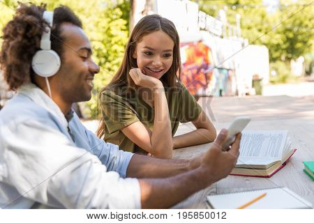 Image of happy young multiethnic friends students talking with each other outdoors using mobile phone. and listening music. Looking aside.