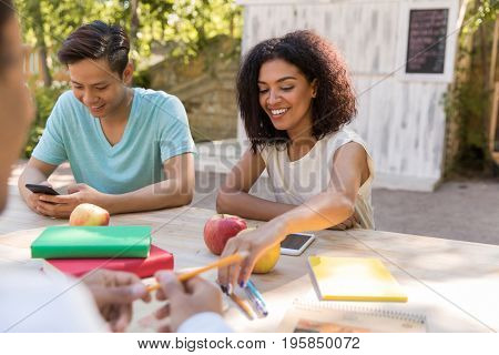 Image of happy young multiethnic group of friends students talking with each other outdoors. Looking aside.