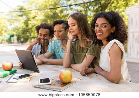 Image of happy young multiethnic friends students outdoors using tablet computer and talking with each other. African lady looking camera.