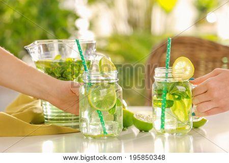 Women taking mason jars of refreshing lemonade on table