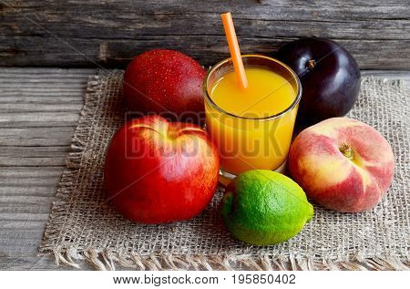 Fresh fruits and a glass of juice.Multi fruit juice.Juice mix fruit on burlap cloth on wooden table.Healthy drink or diet concept.