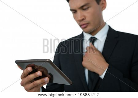 Businessman holding necktie while using tablet computer against white background