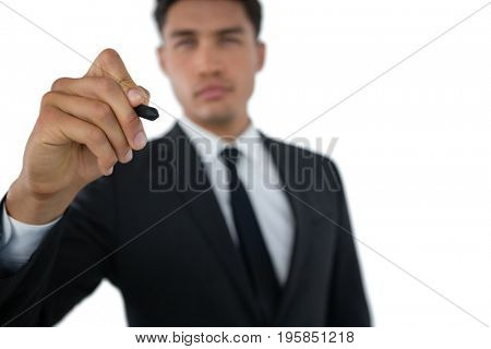 Businessman writing on invisible interface against white background