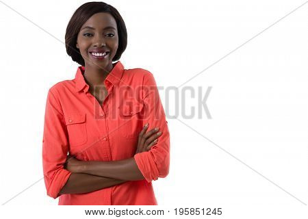 Portrait of young woman with arms crossed standing against white background