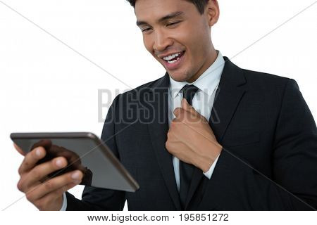 Happy businessman holding necktie while using tablet computer against white background