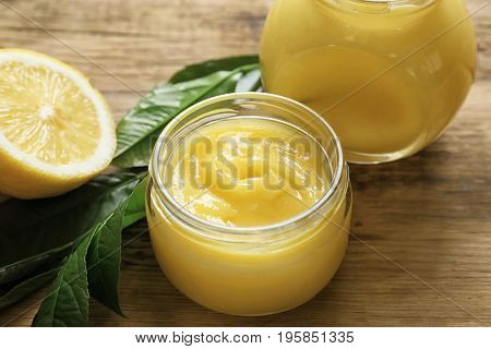 Glass jars with yummy lemon curd on wooden table