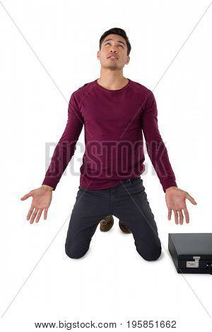 Businessman pleading while kneeling against white background