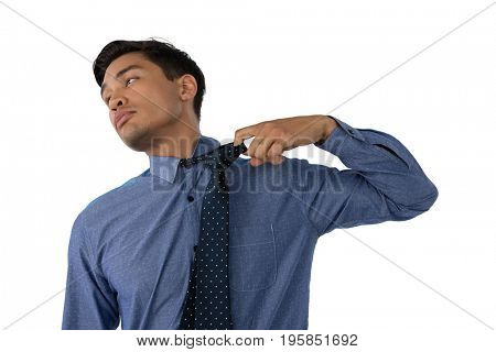 Businessman loosening necktie while standing against white background