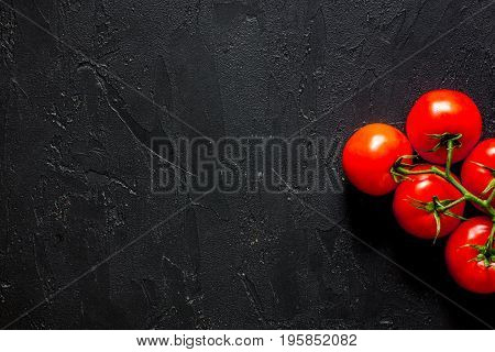 Prepring for cooking dinner. Tomato on black table background top view.