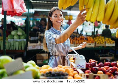 Picture of beautiful woman at marketplace buying fruits