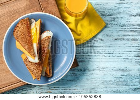 Delicious sandwiches with over easy egg and cheese on kitchen table