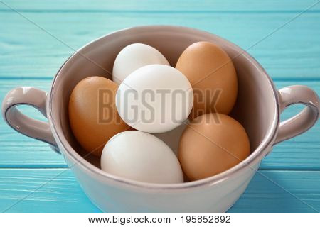 Soup saucer with hard boiled eggs on blue wooden table. Nutrition concept