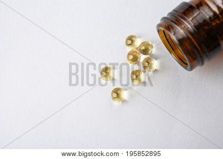 Glass bottle and pills on light background