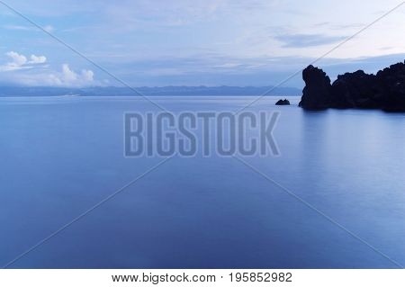 Long exposure image of the rocky coast and the island of Sao Jorge, Azores, Portugal