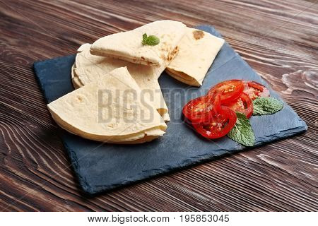 Slate plate with yummy tortillas and sliced tomatoes on wooden table