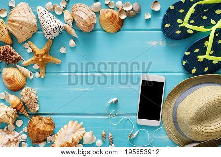 Vacation background on blue wood, top view. Beach accessories, flip flops, smartphone and seashells