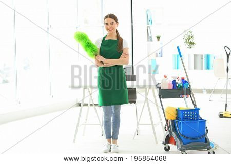 Cleaning service concept. Young woman wearing green apron in office