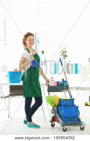 Cleaning service concept. Young woman with bottle of detergent in office