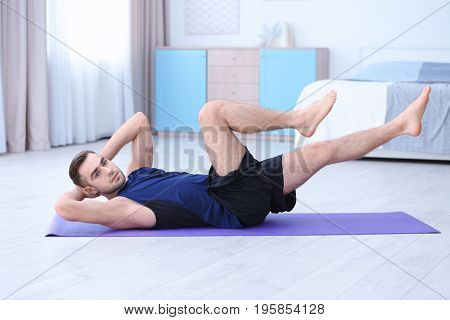 Young man doing bicycle crunch exercise at home