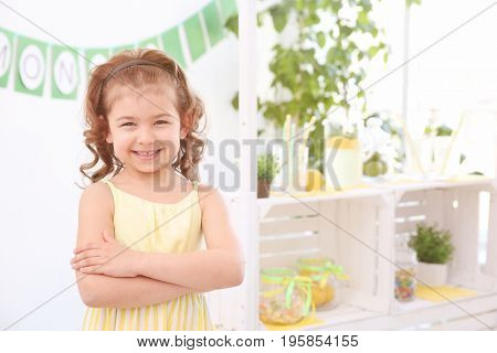 Cute little girl and blurred stand with lemonade on background