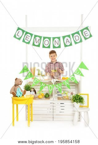 Cute little boy selling lemonade at counter on white background