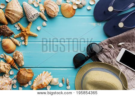 Vacation background on blue wood, top view with copy space. Beach accessories, sunglasses, flip flops, smartphone and seashells
