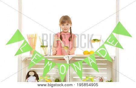 Cute little girl selling lemonade at counter on white background