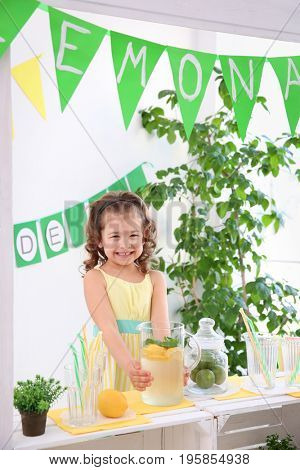 Cute little girl selling lemonade at counter