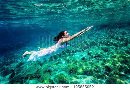 Refreshing swimming underwater, beautiful young woman wearing fashion white long dress and dive into clear transparent sea, luxury summer vacation concept