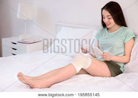 Beautiful young woman with tablet computer and bandaged leg sitting on bed at home