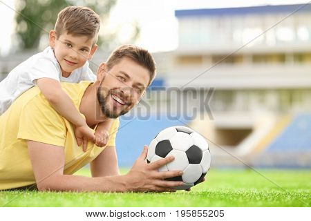 Dad and son with soccer ball in stadium