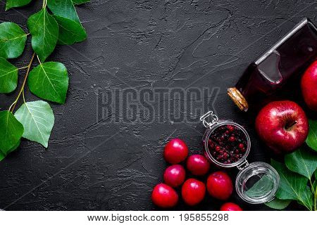 Summer fruit drink with apple, pulm and cranberry on black table top view.