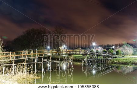Suzdal, Russia. wooden bridge through the Kamenka River to Nativity Cathedral of Suzdal Kremlin at night in summer