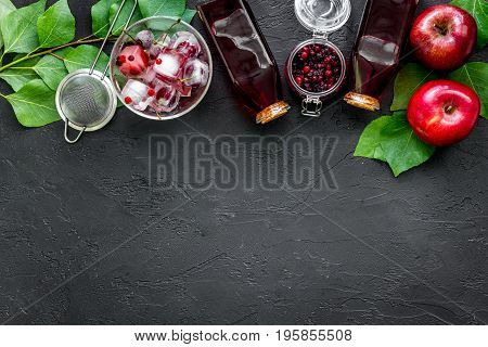 Summer ice fruit drink with apple and cranberry on black table top view.