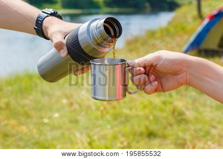 Tea poured into a Cup from a thermos on the background of nature.