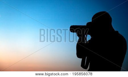 Silhouette of a photographer over blue sky background, professional photographer making picture, traveler taking photo, man at work, creative profession