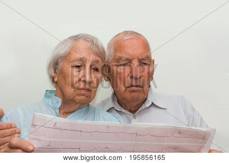 The medicine, age, health care and people concept - the sad senior woman and man looking at cardiogram on gray background