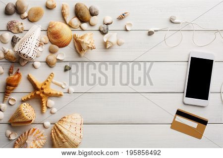 Vacation background on white wood, top view with copy space. Online shopping on smartphone.