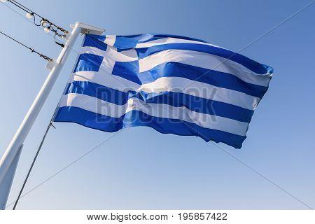 Greek national flag waving on the wind against blue sky.
