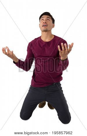 Businessman gesturing while kneeling against white background