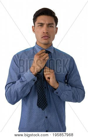 Portrait of young businessman adjusting necktie while standing against white background
